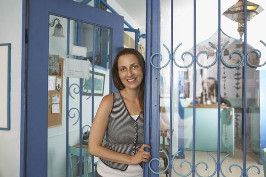 Portrait of female owner standing at the entrance of restaurant
