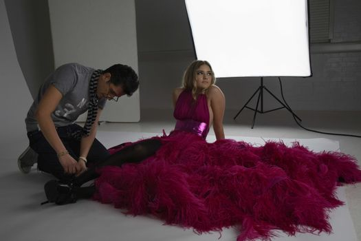 Side view of a male designer adjusting fashion model's shoe in studio