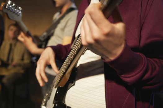 Closeup midsection of male guitarists in performance