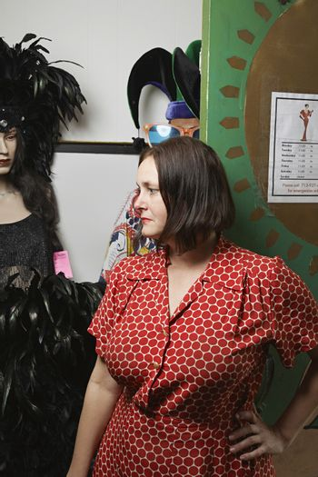 Second Hand Store Owner Standing by Costumes