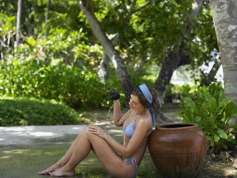 Young Woman in Bikini Pouring Water on Self
