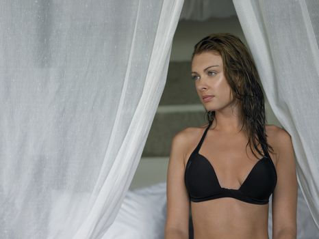 Young Woman in Bikini by Canopy Bed