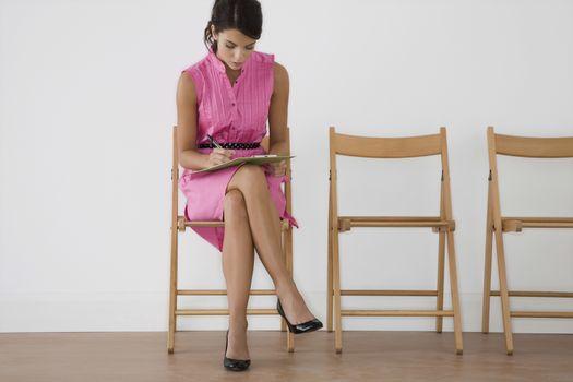 Woman in pink dress writing