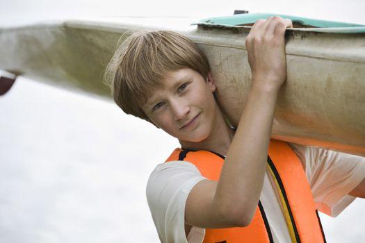 Teenage boy carrying kayak