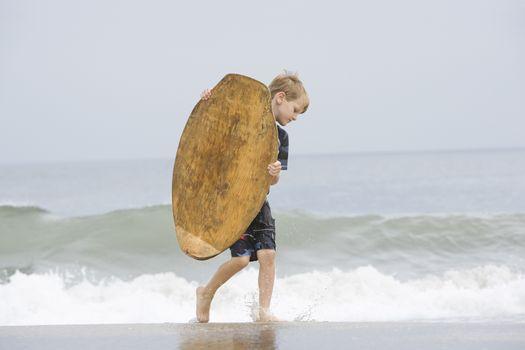 Little Boy Carrying a Bodyboard