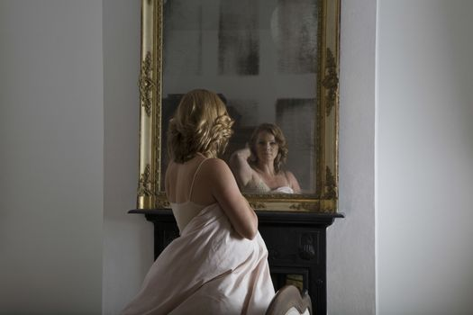 Woman dressed in quilt examining herself in mirror