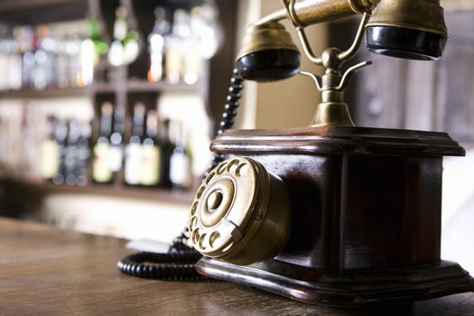 Closeup of a wood and brass antique dial telephone on bar counter