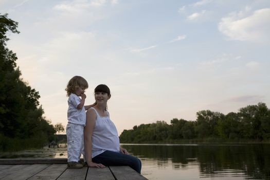 Pregnant Mother And Daughter Sitting On Jetty In Evening