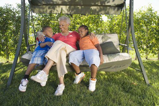 Grandmother with grandchildren on outdoor swinging chair
