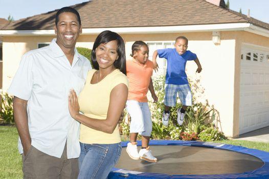 Family outside house children on trampoline