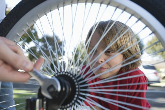 Boy watching father fix bicycle tyre