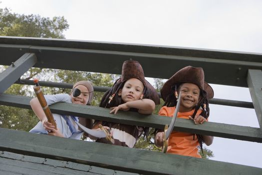 Three boys (7-9) wearing costumes looking down from bridge