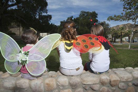 Three girls (7-12) wearing costumes sitting in park