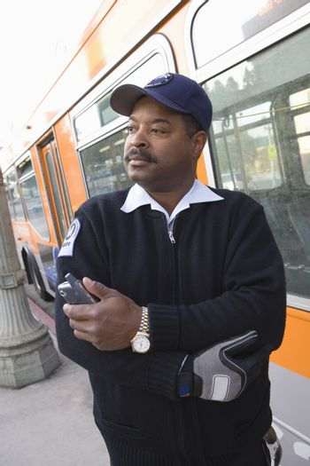 Bus driver holding mobile phone by bus
