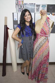 Portrait of female fashion designer with dress