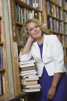 Portrait of female librarian by bookshelf