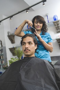 Hairdresser cutting mans hair
