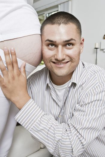 Smiling man with head at pregnant woman's abdomen