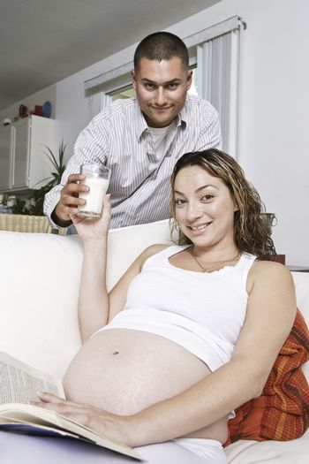 Portrait of expectant couple man serving glass of milk to woman