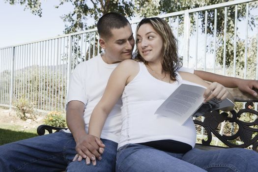 Expectant couple relaxing on bench