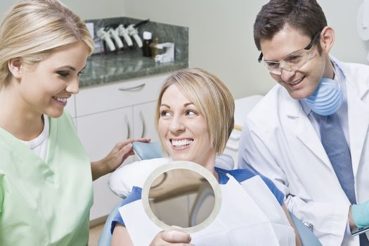 Happy dentistry team with female patient using mirror in clinic