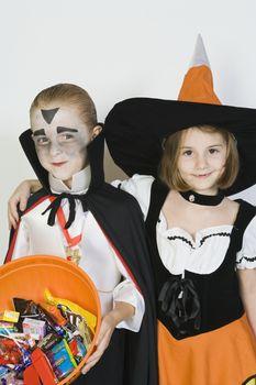 Portrait of girl embracing boy (7-9) wearing Halloween costumes