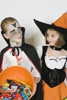 Girl and boy (7-9) wearing Halloween costumes studio shot