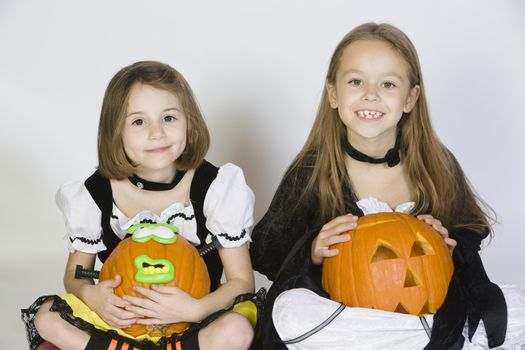 Portrait of girls (7-9) wearing Halloween costumes with jack-o-lanterns