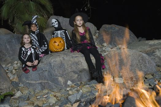 Portrait of boys and girls (7-9) wearing Halloween costumes by campfire