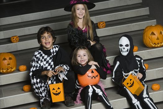 Portrait of boys and girls (7-9) wearing Halloween costumes on steps
