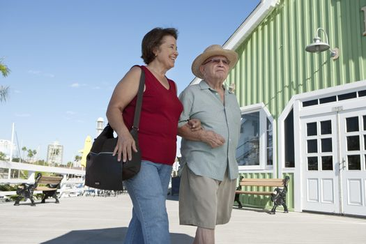 Senior couple on vacations walking arm in arm
