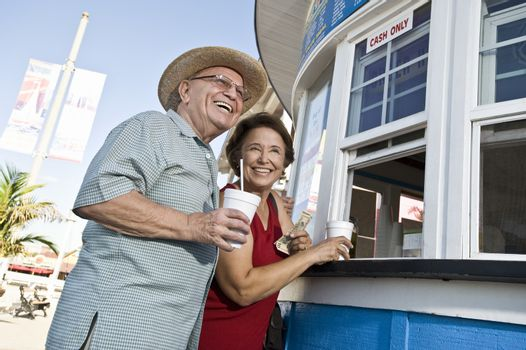 Senior couple buying drinks at food stand