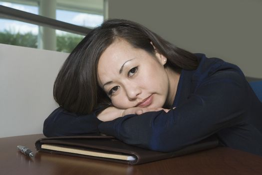 Bored Asian Businesswoman with Head on Desk