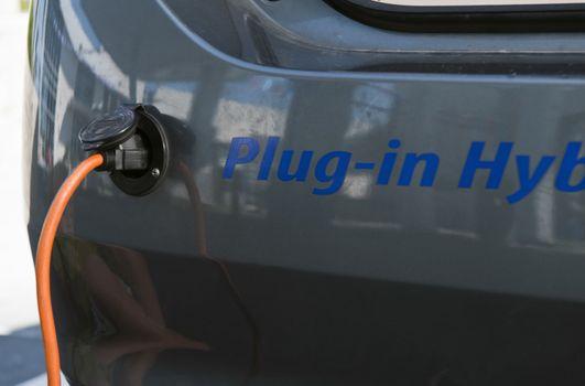 Closeup shot of electrical plug recharging electric car