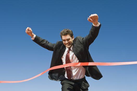 Businessman Crossing the Winning Line