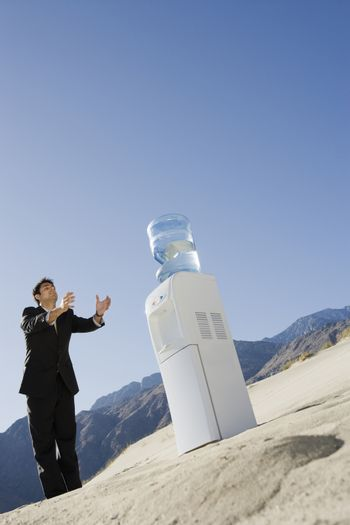 Businessman Standing by Water Cooler in the Desert