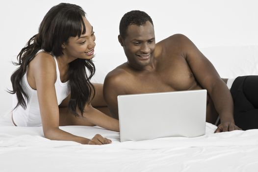 Mid adult couple using laptop in bedroom