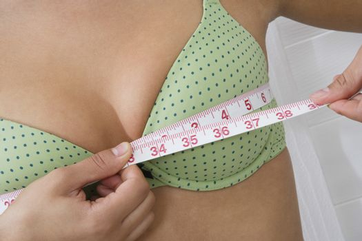 Closeup midsection of a young woman measuring breasts