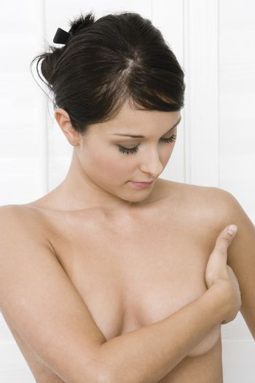 Naked young woman examining breast