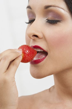 Closeup of an seductive woman eating strawberry