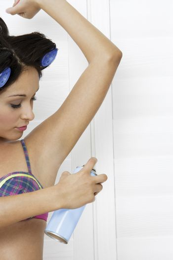 Closeup of a cropped young woman using deodorant in armpit