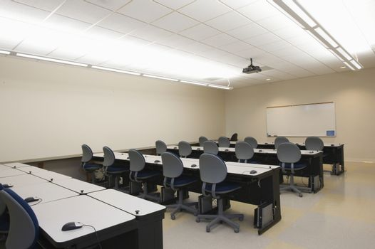 Empty chairs and tables in front of whiteboards in seminar room