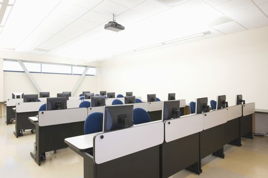 View of empty chairs and computers in rows at seminar room
