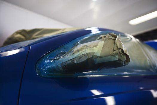Closeup of damaged headlight of a blue car
