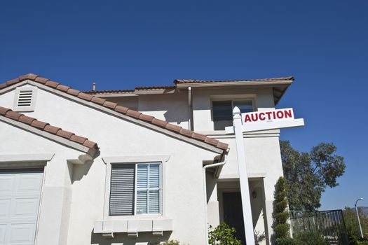 Residential structure with 'Auction Sign' against sky