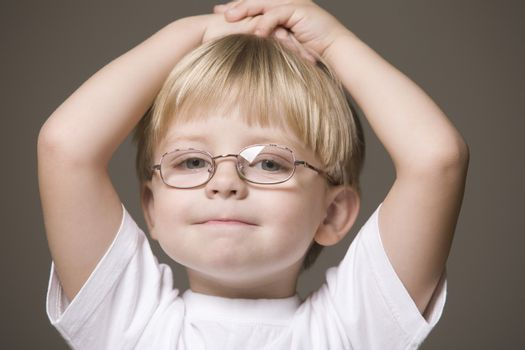 Blonde-haired boy wearing glasses with hands on head