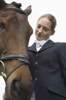 Female horseback rider with horse outdoors
