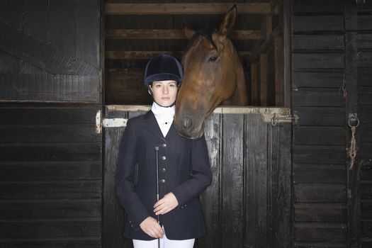 Portrait of Female horseback rider with horse in stable