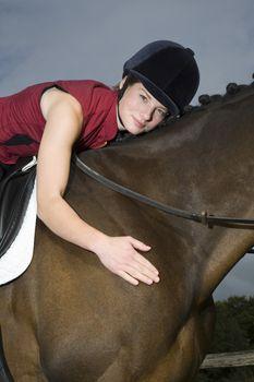 Female horseback rider hugging horse