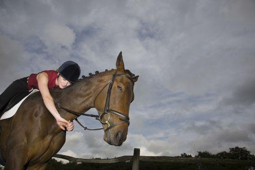 Female horseback rider embracing horse